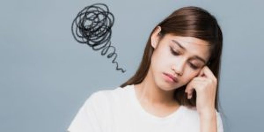 Depressed brunette girl with head leaning on hand with a squiggly black line like a dialogue bubble on left side of her