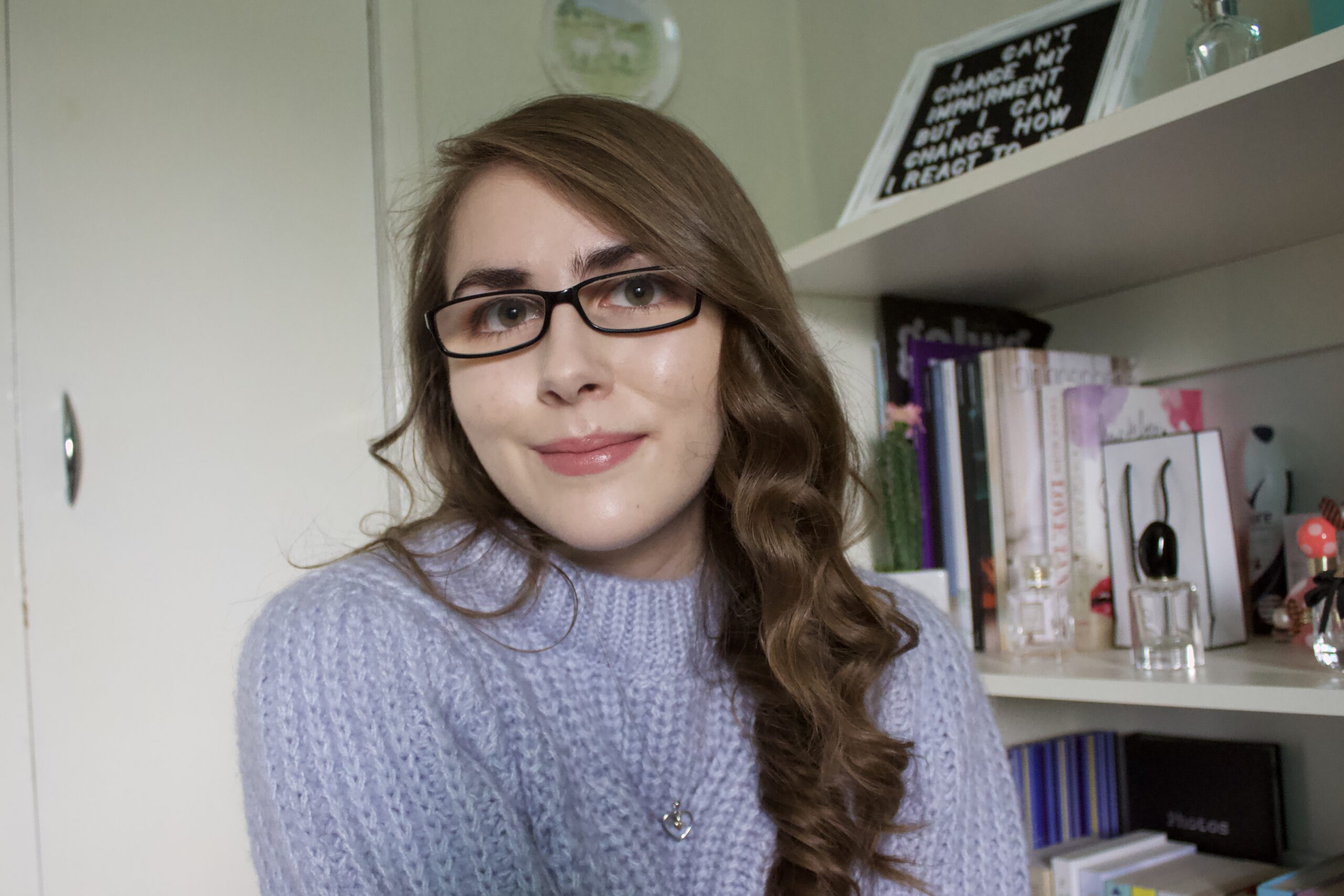 Elin sitting in front of a white bookcase, she's wearing a lilac knitted jumper and a dainty silver heart shaped necklace