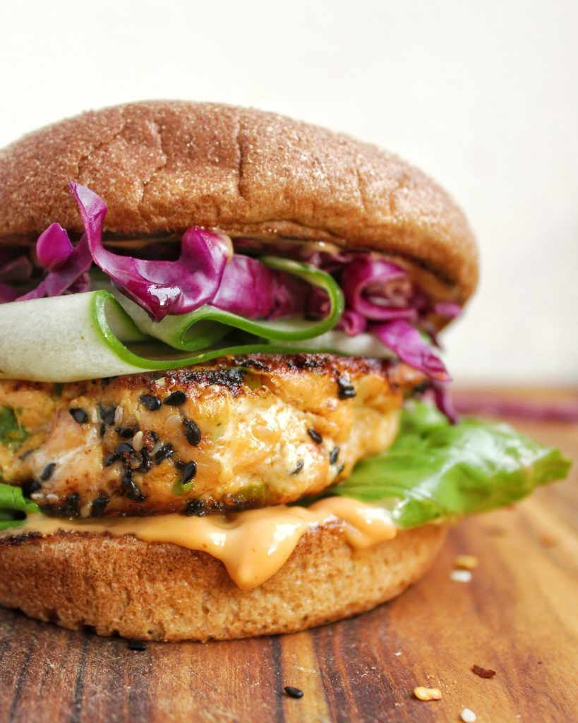 Spicy Sesame Salmon Burger topped with cucumber, spicy mayo and red cabbage