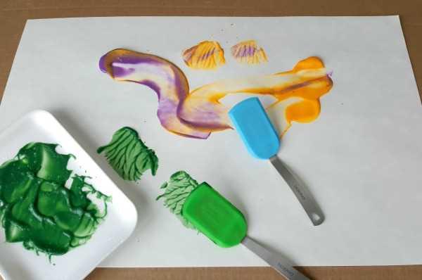 toddler painting using spatulas process art