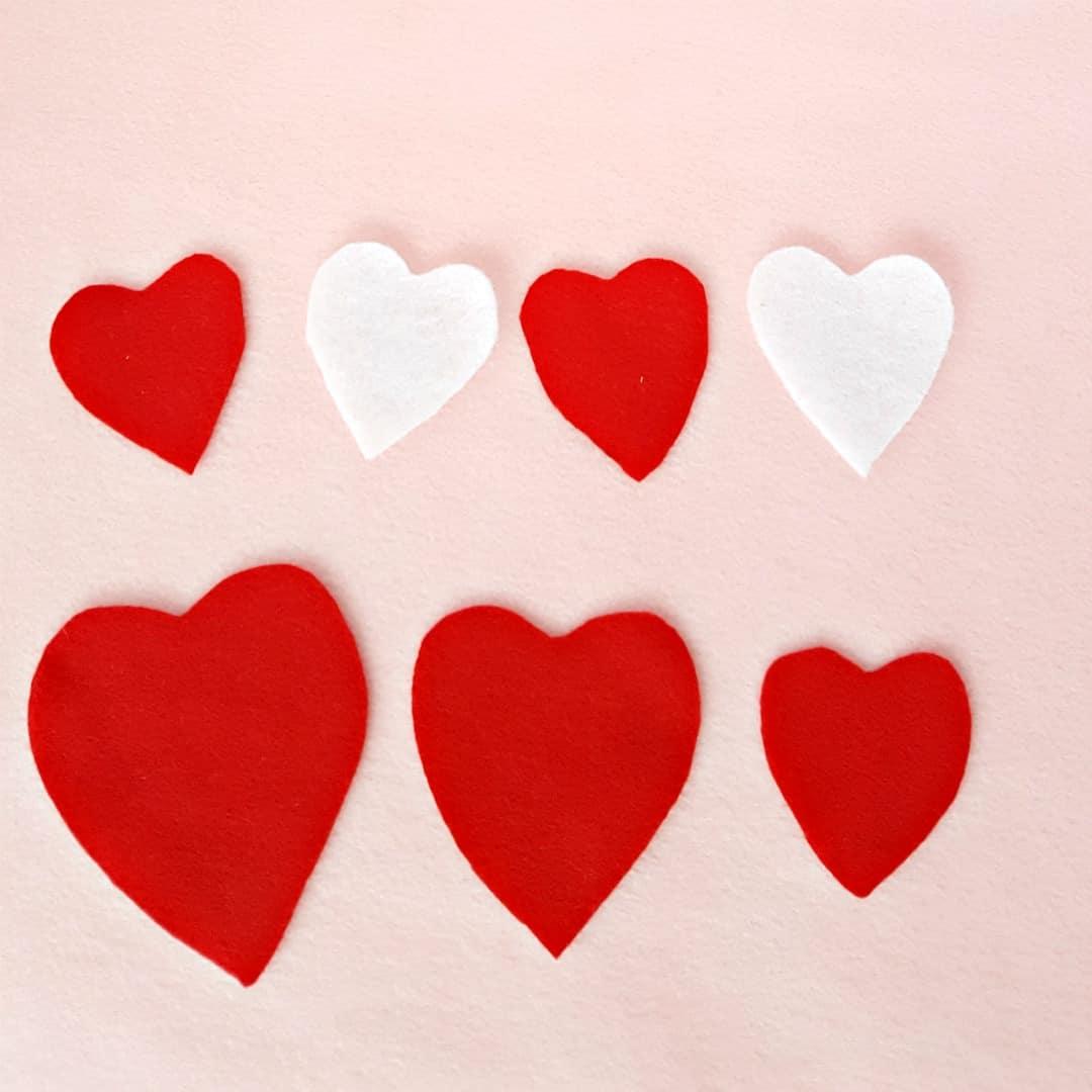 Arrange hearts in patterns toddler Valentine's day heart felt board activity
