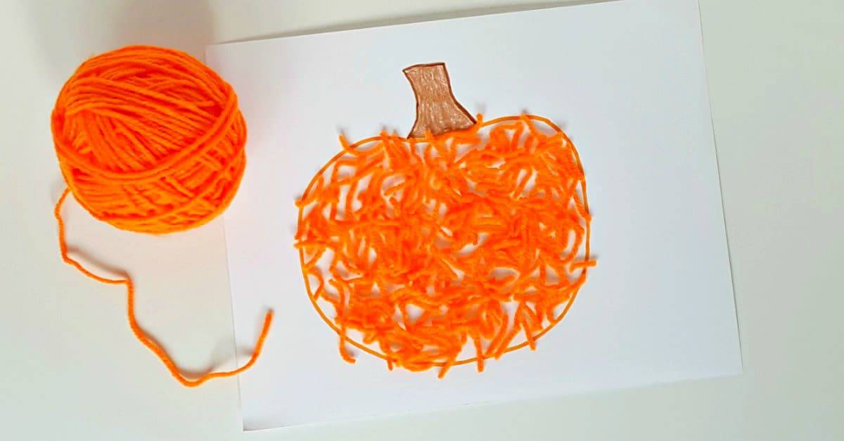 Fall pumpkin toddler craft with orange yarn