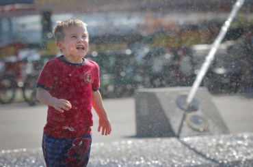 little boy in fountain in downtown portland