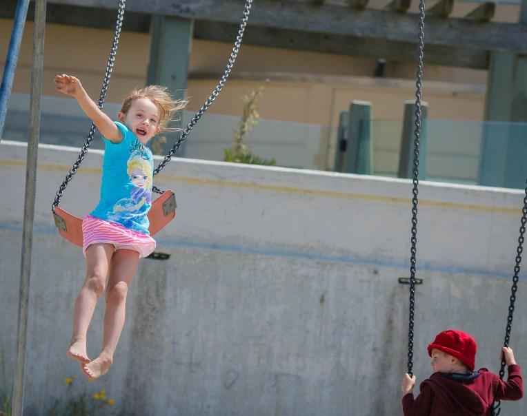 little girl jumping off swing