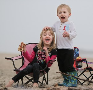 two kids on the beach eating picnic