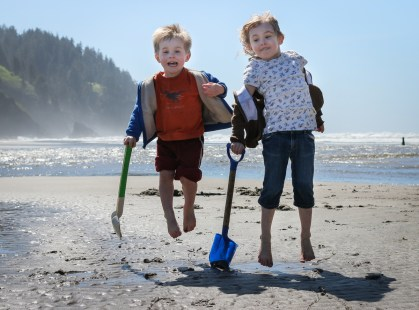 two little kids jumping on the beach