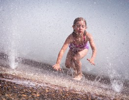 girl in fountain with water droplets in air