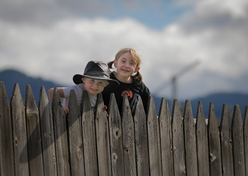 brother and sister looking over fence