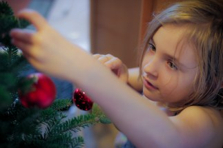 little girl putting ornament on Christmas tree