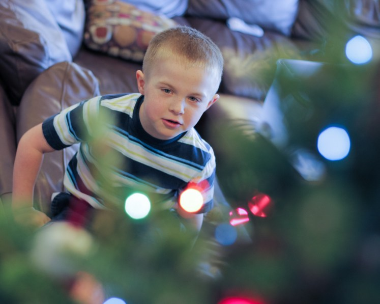 little boy decorating Christmas tree