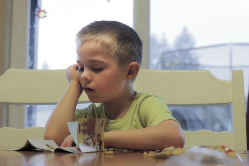 little boy pondering Lego set instructions