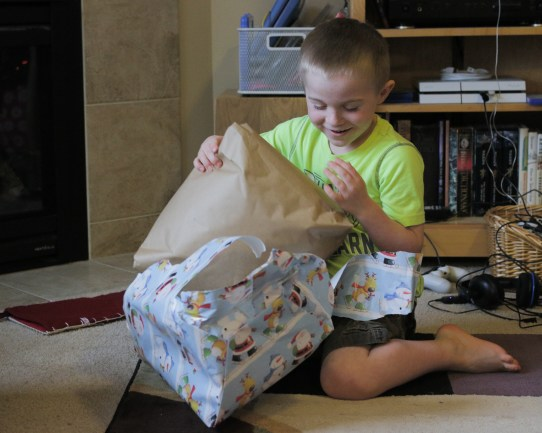 little happy boy opening a Christmas present