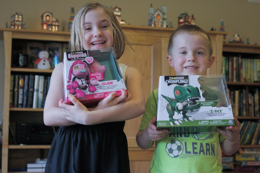 brother and sister showing off Christmas presents