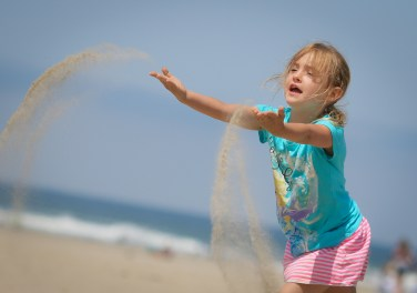 girl throwing sand at beach
