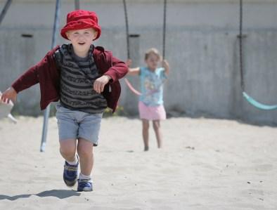 little boy running on beach