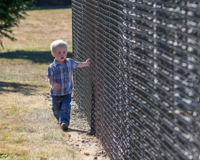 little boy walking by chain link fence