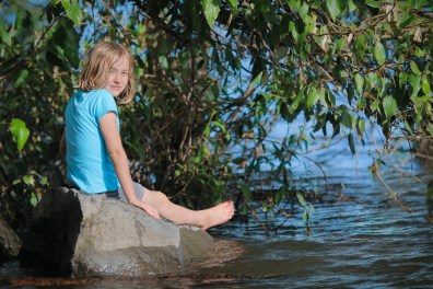 little girl sitting on a rock on edge of river