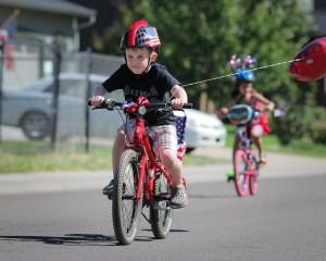 little boy riding bike with mohawk helmet