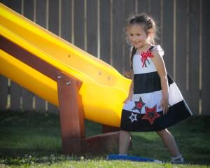 little girl by yellow slide