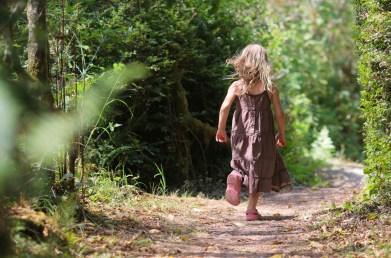 little girl running in woods