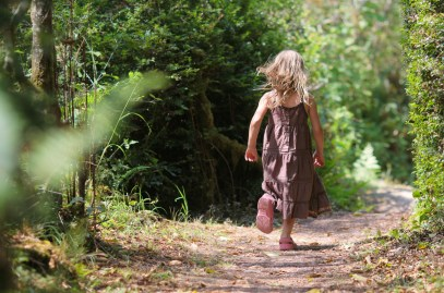 little girl running in woods