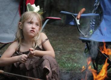 little girl roasting hot dogs