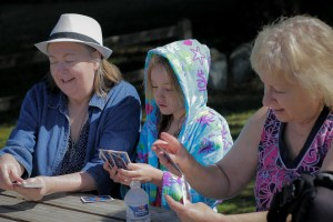 grandmas and granddaughter playing cards