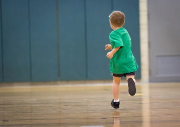 little boy running down basketball court