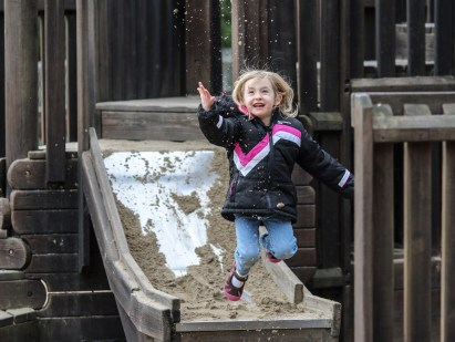 girl jumping off slide throwing sand