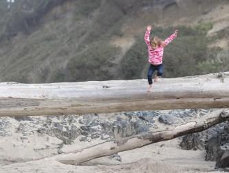 girl jumping off high log