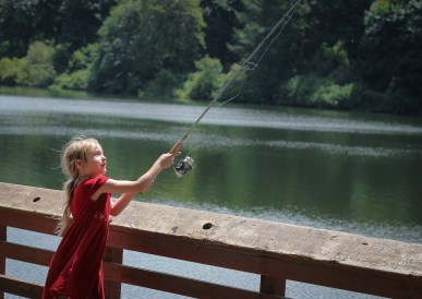 little girl casting a fishing pole