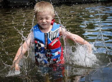 little boy splashing in the water with eyes closed