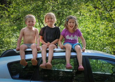three little kids sitting on top of car
