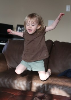 little girl flying off couch