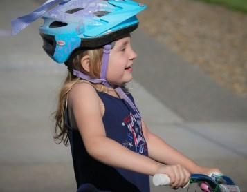 little girl on bike with helmet