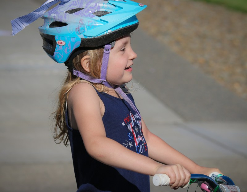 little girl on bike with helmet