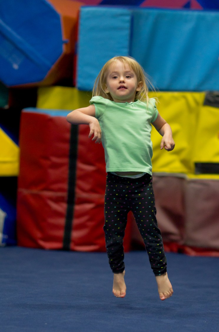 little girl jumping in air at gymnastics