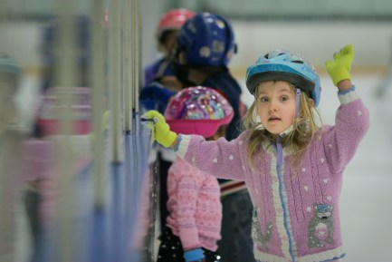 little girl ice skating by wall