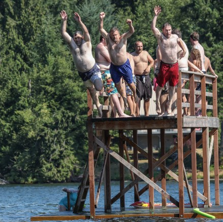 men jumping off raised dock