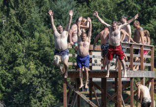 men jumping off a high dock