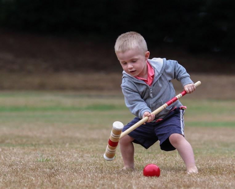 little boy playing croquet
