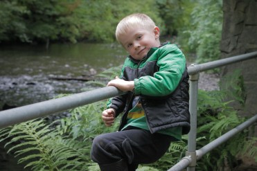boy hanging on rail by river