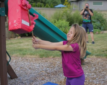 girl hitting pinata