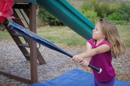 girl hitting pinata with bat