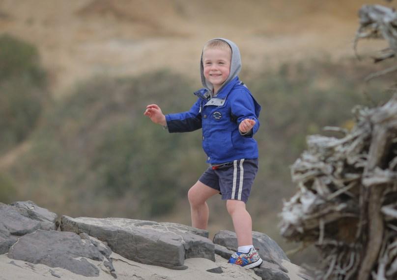 smiling boy on beach rocks