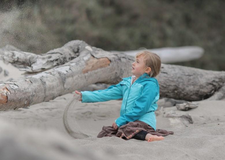 little girl throwing sand on beach