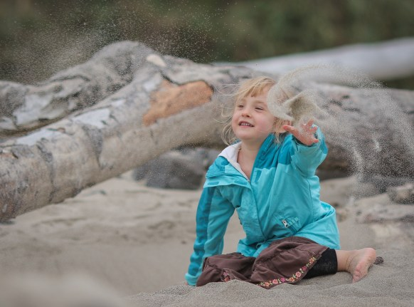 Alaina throwing sand on beach