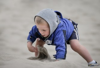 kid digging hole in sand at beach