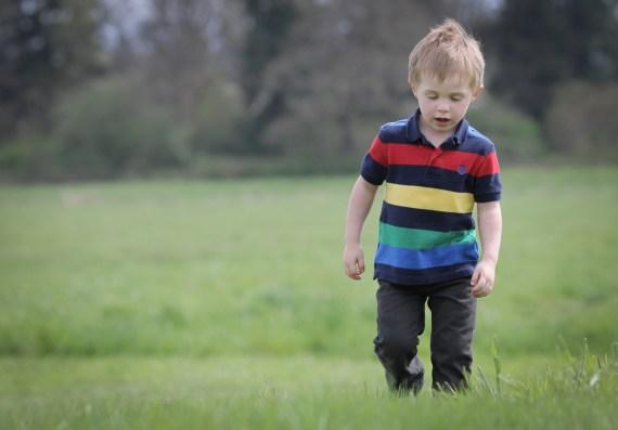 kid walking through green grass
