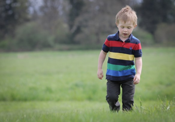 kid walking through green grass